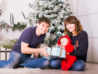 Happy family holding Christmas gifts near Xmas tree. Baby, mother and father having fun at home