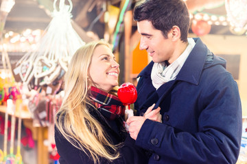 Couple with sweet apple on Christmas market