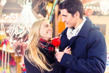 Couple with sweet apple on Christmas market