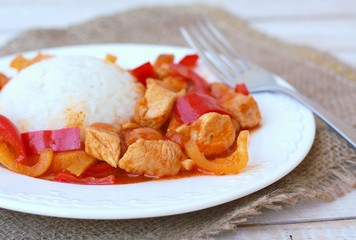Meal from chicken meat with Indian spices, green and red pepper and rice on white plate, gunny cloth and wood with fork