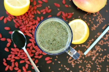 Healthy fresh smoothie drink from red Chinese berry goji, lemon, green spirulina, linseed and apple