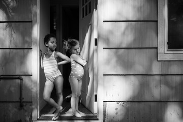 Portrait of two children standing in doorway, black and white