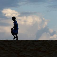 Boy walking on sand dune at Mingsha Shan, Dunhuang, Jiuquan, Gan