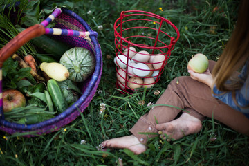 Young girl sitting in garden with vegetables and eggs