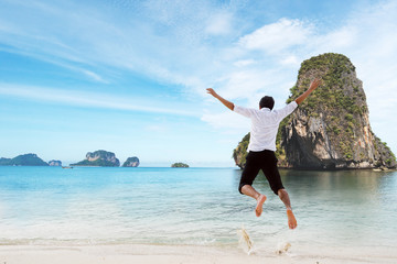 Happiness of businessman jumping relax on beautiful sea beach at
