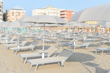 Light sunbeds, loungers and beach umbrellas on empty sand beach
