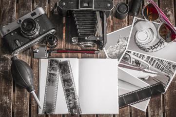 Retro Fotokameras auf einem Tisch / Alte Retro Fotoapparate auf einem Tisch mit Fotografien, Negativen und Filme mit Textfreiraum.