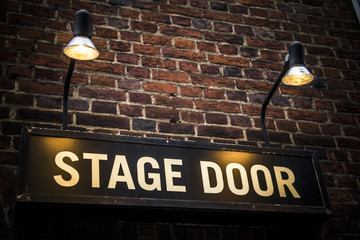 Stage door sign lit by spotlights at theatre venue