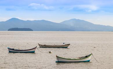 Três canoas no mar.