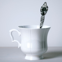 Vintage porcelain cup with silver spoon on white background.  3d