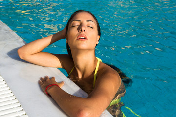 Beautiful woman with water dripping face resting by the pool.