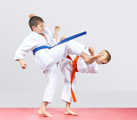 On a light background two boys are beating karate kicks