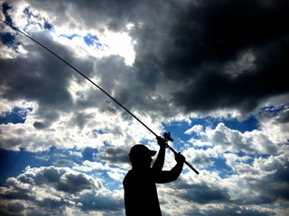 Silhouette of fisherman throwing fishing rod in lake