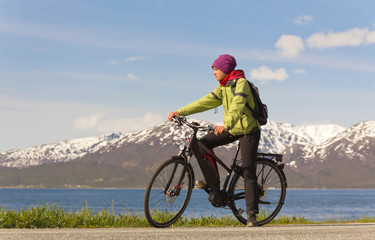 junge Frau sitzt auf Fahrrad vor Bergkulisse