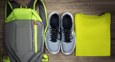 Set for sports shoes, backpack, t-shirt close-up on a wooden background, top view