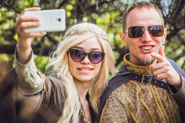 Handsome man with beard and young pretty cheerful girl with glasses making selfie.