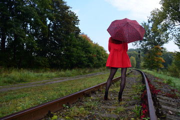 Rear view of a girl with an umbrella in a red coat