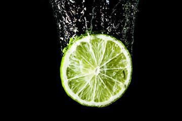 Lime slice splashing into water.
