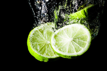Lemon slice splashing into water.