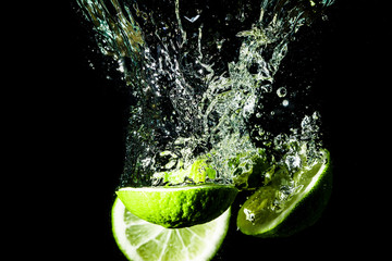 Lemon slices splashing into water.