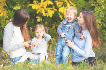 Alternative lesbian family with mothers, daughter and boy outdoor