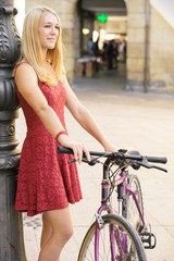 Young girl with bicycle leaning on a lamppost