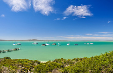 Foto auf Leinwand Südafrika Stunning view of Langebaan Lagoon in West Coast National Park,120 km north of Cape Town, Western Cape Province, South Africa. Sunny day, house boats, a jetty and mountains in the background.