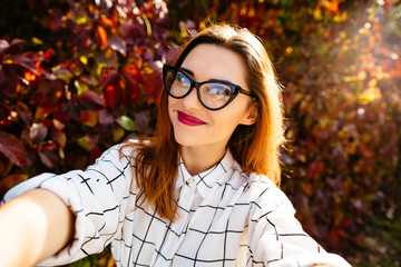 Autumn selfie portrait of a beautiful girl in glasses.