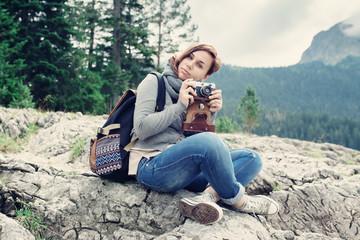 Woman traveler with vintage camera sitting on rocks, nature landscape