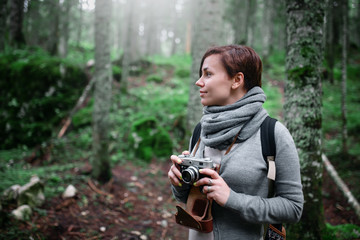 Woman with vintage camera taking photo in the forest