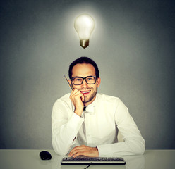 man sitting in front of computer keyboard with light bulb over head.