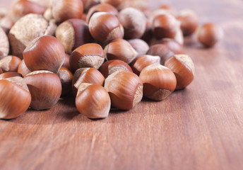 Hazelnuts on wooden background. Focus on the foreground