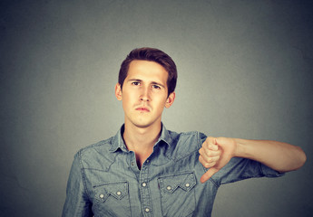 angry young man showing thumbs down sign, in disapproval