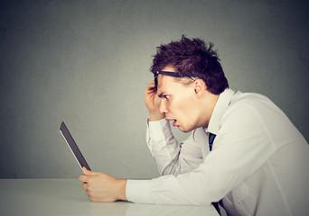 Side profile shocked man looking at laptop computer