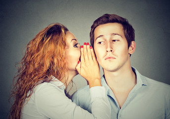 Speak in the ear. Woman whispering to handsome guy