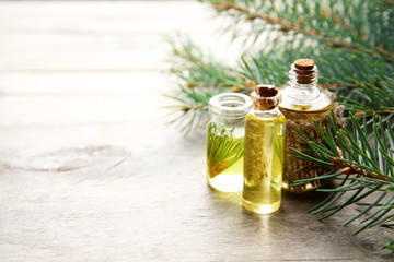 Bottles of coniferous essential oil and branches on wooden background, close up view