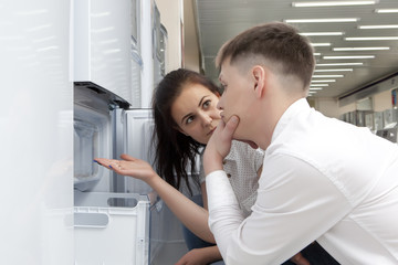 Happy family couple looking at large fridges