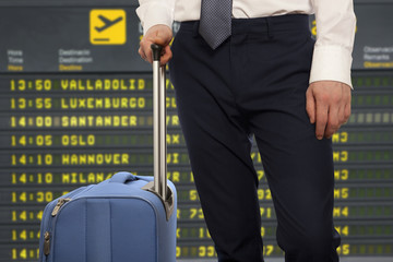 Businessman with travel bag over airport background