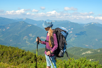 Young girl with backpack in mountains