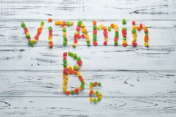 From pieces of colored candied fruits laid out the word vitamin B5.