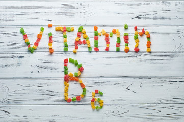From pieces of colored candied fruits laid out the word vitamin B6.