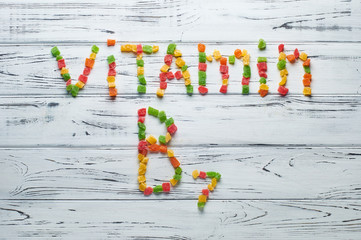 From pieces of colored candied fruits laid out the word vitamin B7.