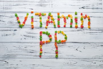 From pieces of colored candied fruits laid out the word vitamin PP.