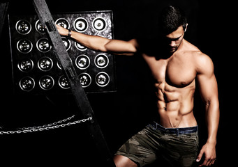 Portrait of strong healthy handsome Athletic Man Fitness Model posing on black background