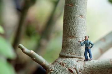 Toy lumberman / View of miniature toy, lumberman standing on tree. Focus on lumberman.