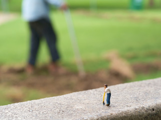 Toy worker / View of miniature toy, worker standing in the park.