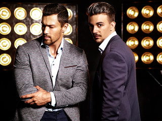 portrait of two sexy handsome fashion male models men dressed in elegant suits on black studio lights background