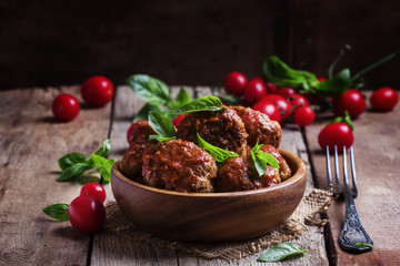 Meatballs of pork and beef with spicy tomato sauce in bowl, vint