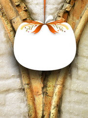 Close-up of one blank pumpkin shaped frame hanged by orange ribbon on old weathered stone arch detail