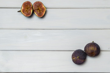 Whole and cut fresh vibrant figs fruit on white wooden background from above